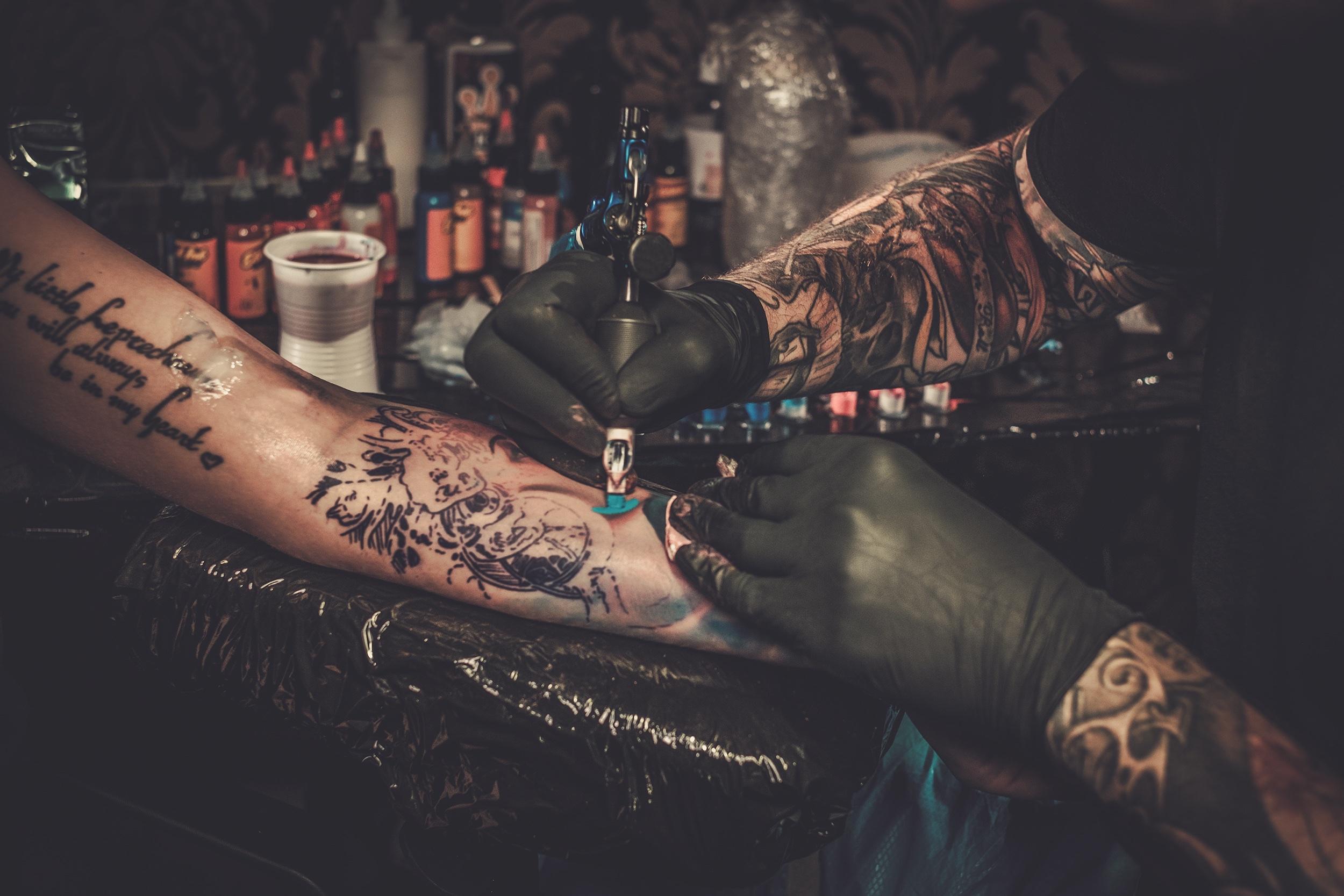 Professional tätoveering kunstnik teeb tätoveering noor tüdruk käsi.